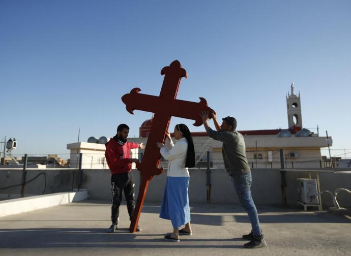 Fedeli issano una croce a Qaraqosh in attesa del Papa