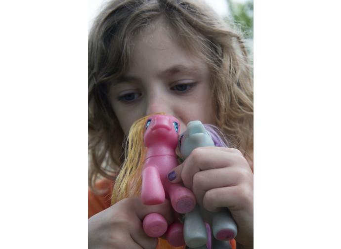 Una bimba gioca con un pupazzo