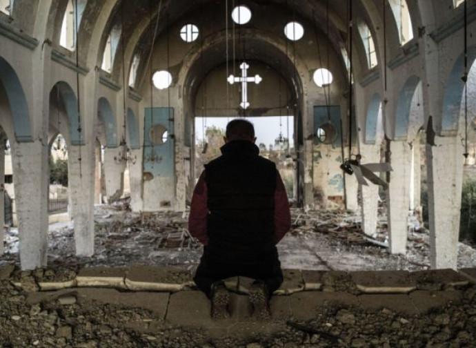 Fedele in preghiera nella chiesa di Hasakah, Siria, distrutta dall'Isis