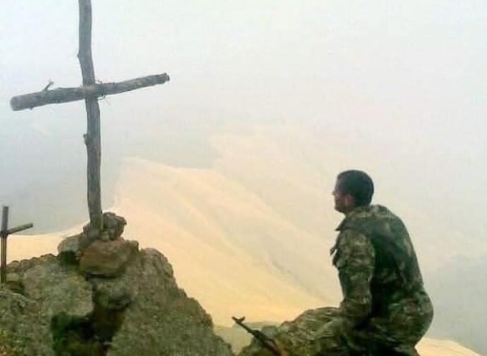 Soldado reza na frente da cruz