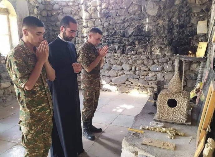Um padre reza com os soldados