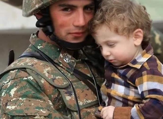 Jovem soldado protege uma criança