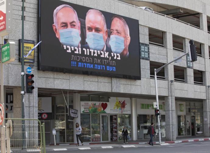 Tel Aviv, poster con Netanyahu, Lieberman e Gantz con mascherina