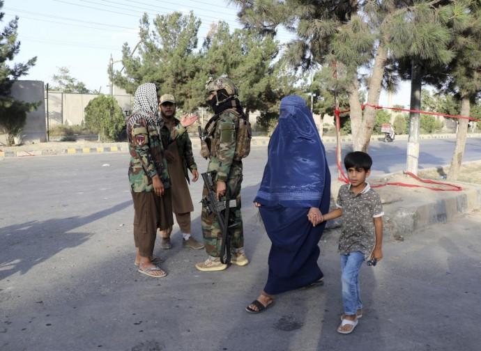 Talebani armati e donna in burqa. Il futuro dell'Afghanistan